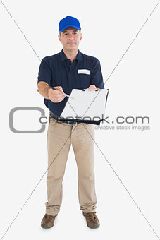 Mature delivery man holding out clipboard