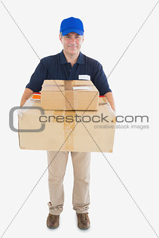 Mature courier man carrying stack of cardboard boxes
