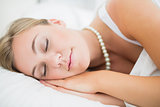 Sleeping cute woman with pearls necklace