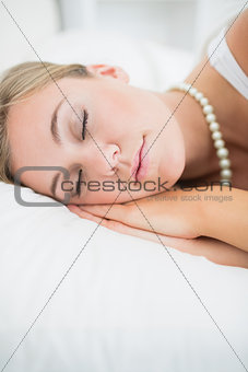 Close to a sleeping woman with pearls necklace