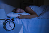 Focus on the alarm clock in front of sleeping woman