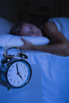 Alarm clock in front of a sleeping woman