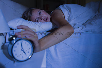 Awakening woman stopping her alarm clock