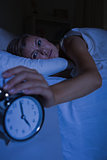 Blonde woman stopping her alarm clock