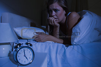 Unquiet blond woman in the bed at night