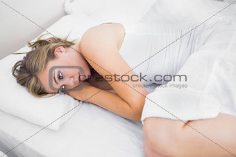 Blonde woman thinking in the bed