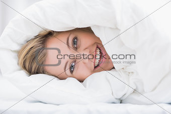 Happy woman hiding under the duvet