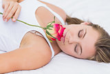 Blonde woman lying on the bed with a rose