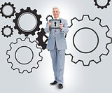 Businessman standing against a cogs background