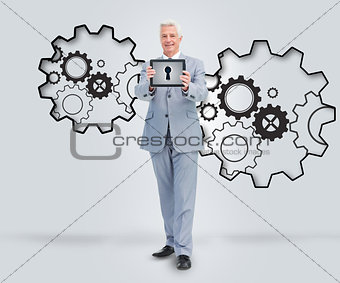 Smiling businessman holding a tablet against a background