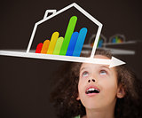 Surprised girl looking up at energy efficient house graphic