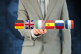 Businessmans finger activating futuristic touchscreen with various flags