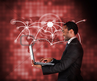 Smiling businessman holding laptop against a background