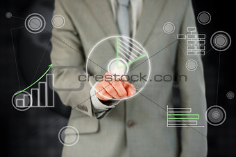 Businessman activating touchscreen against a black background