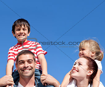 Happy parents giving their children piggyback rid