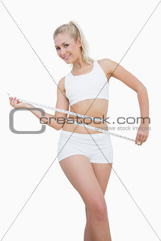 Happy young woman measuring waist