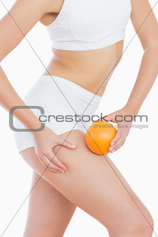 Fit woman squeezing fat on thigh as she holds orange