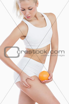 Woman checking out fat on thigh as she holds orange