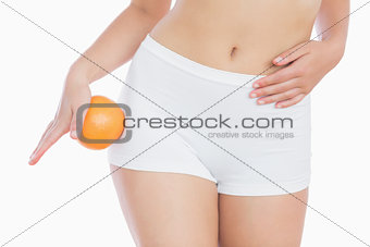 Fit female in shorts with fresh orange