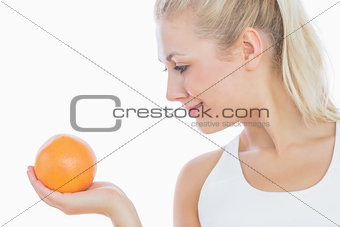 Woman looking at fresh orange