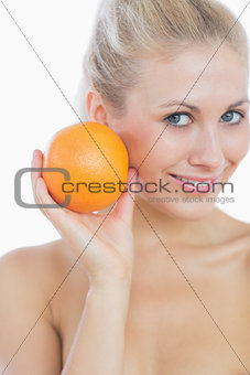 Happy woman holding fresh orange