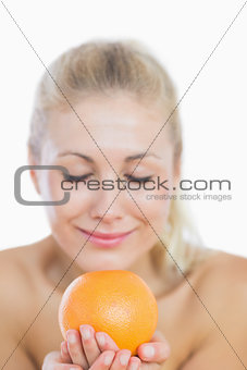 Happy woman smelling fresh orange