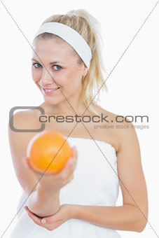 Happy young woman holding orange