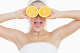 Surprised woman holding orange slices in front of eyes