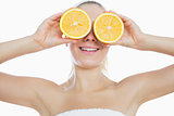 Woman holding slices of orange in front of eyes