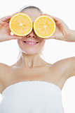 Happy woman covering eyes with slices of orange
