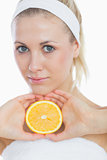 Attractive woman holding slice of orange