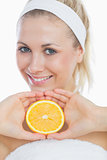 Happy young woman holding slice of orange