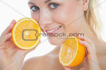 Beautiful woman holding slices of orange