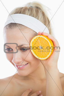 Fresh and happy woman holding slice of orange