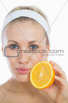 Portrait of woman holding orange slice