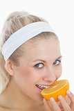 Woman biting slice of orange