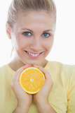 Happy woman showing slice of orange