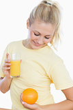 Woman holding orange and glass of juice