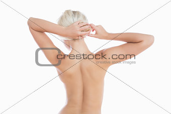 Topless woman tying hair