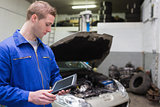 Mechanic with digital tablet at garage