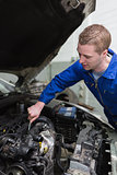Car mechanic working on engine
