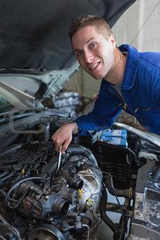 Mechanic working under bonnet of car