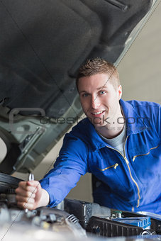 Auto mechanic working on motor