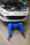 Male mechanic lying under car