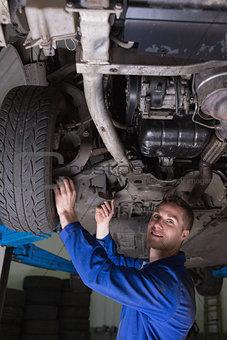 Happy mechanic under car