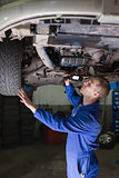 Male mechanic examining car