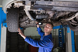 Mechanic with flashlight under car