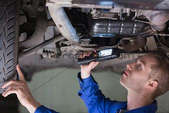 Young mechanic examining car