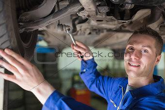 Portrait of mechanic working under car