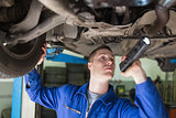 Mechanic with frashligth examining car
